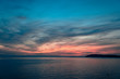 Sunset over the sea, colorful clouds, wide shot. Romantic picture full of colors.