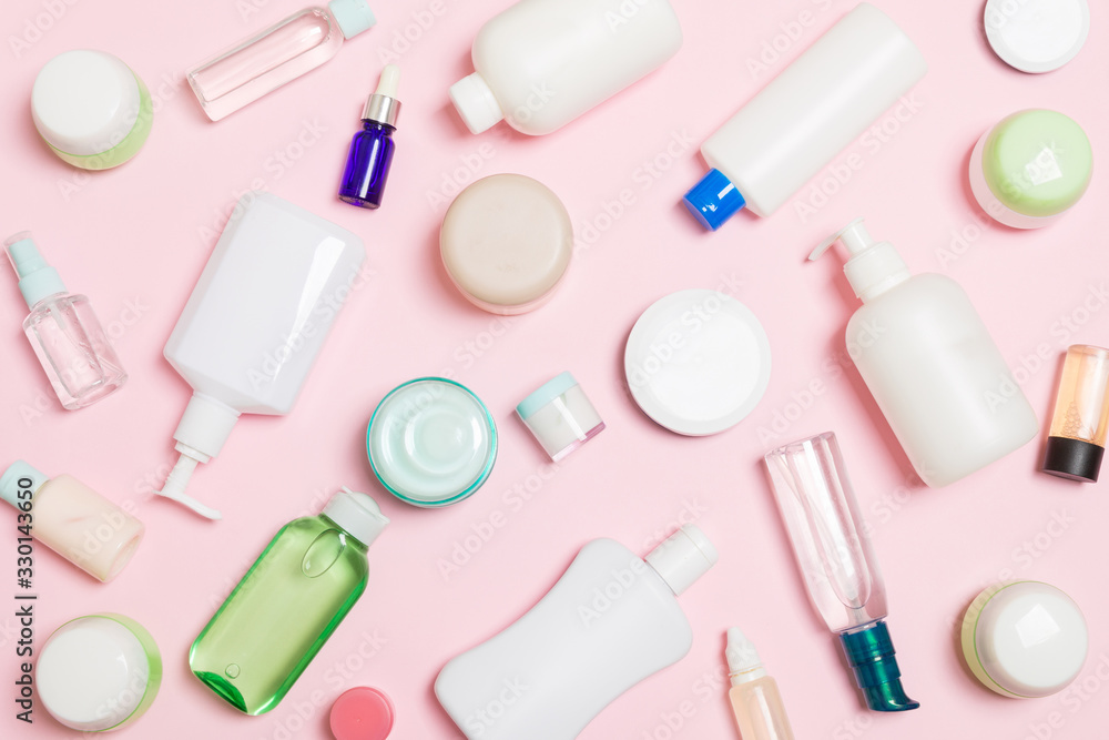 Fototapeta Group of plastic bodycare bottle Flat lay composition with cosmetic products on pink background empty space for you design. Set of White Cosmetic containers, top view with copy space