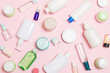 canvas print picture - Group of plastic bodycare bottle Flat lay composition with cosmetic products on pink background empty space for you design. Set of White Cosmetic containers, top view with copy space
