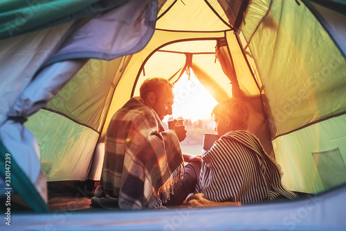 Obraz Father and son drink hot tea sitting together in camping tent. Traveling with kids and active people concept image. - fototapety do salonu