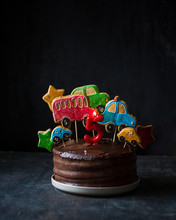 Chocolate Cake Decorated With Gingerbread With The Image Of Cars. Dark Background, Minimalism.
