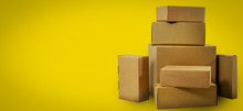 Shipping And Delivery - Blank Cardboard Boxes On Yellow Background With Copy Space