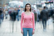 The young woman with medical mask on her face stands in the middle of human flow