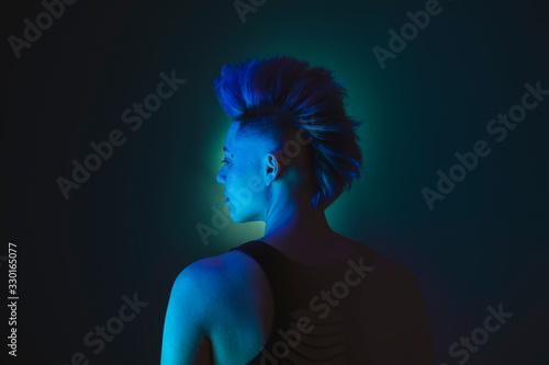 Photo Portrait of a punk lesbian woman with a mohawk blue hairdo
