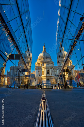 Photo London, England - December 31 2020 - An early morning photo of St Paul's Cathedral with two glass fronted buildings reflecting it and forming a architectural canyon and jet trails in the sky