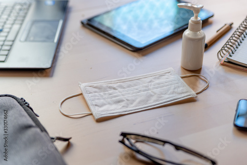 Obraz remote work kit on wooden office desk with hand sanitizer and face mask, a solution against the spread of corona virus for quarantined employees - fototapety do salonu