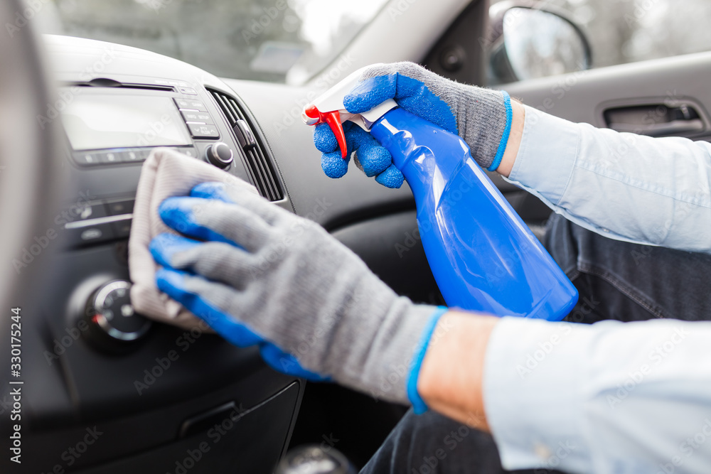 Fototapeta Man cleansing car dashboard and spraying with disinfection liquid.
