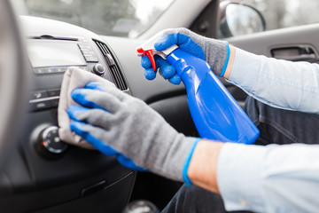 Man cleansing car dashboard and spraying with disinfection liquid.