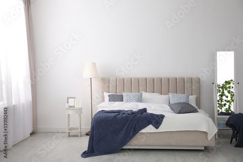 Obraz Comfortable bed with pillows in room. Stylish interior design - fototapety do salonu