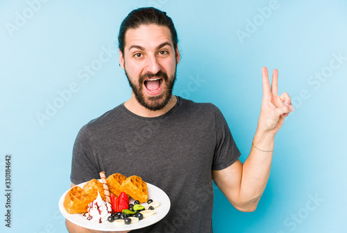 Young caucasian man eating a waffle dessert isolated joyful and carefree showing a peace symbol with fingers.