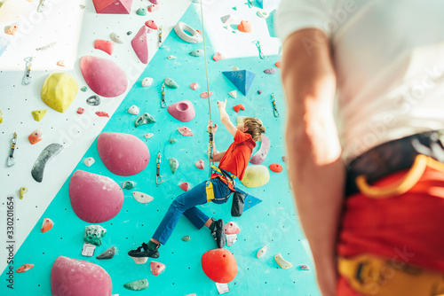 Father and teenager son at indoor climbing wall hall Canvas Print
