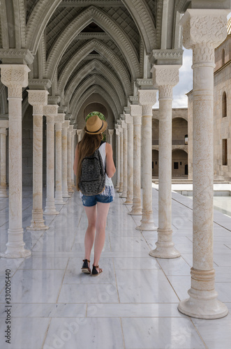 Fotografie, Obraz Young woman walks along the ancient gallery with columns