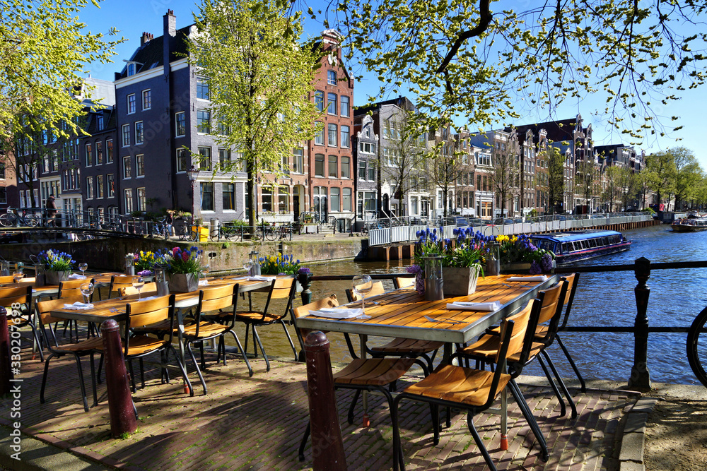 Fototapeta Restaurant tables lining the beautiful canals of Amsterdam under blue skies during springtime, Netherlands