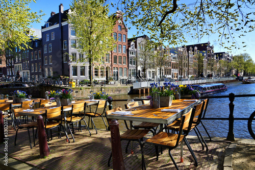 Photo Restaurant tables lining the beautiful canals of Amsterdam under blue skies duri