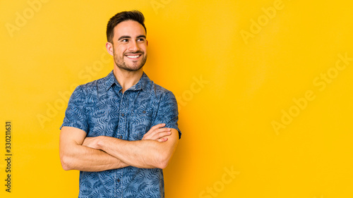 Obraz Young caucasian man isolated on yellow bakground smiling confident with crossed arms. - fototapety do salonu