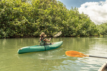 Girl, Woman, Left, Paddling A Green Kayak On A Calm River With Trees Line The Bank And Puffy Clouds In The Sky, Wailua River, Kauai, Hawaii