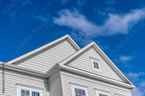 Double gable, with white decorative trim over the windows on a triangle gable ro Canvas Print
