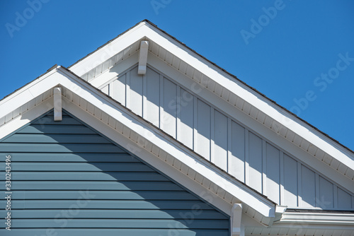 Fototapeta Double gable, with white decorative corbel, bracket, brace on a triangle gable roof, white soffit and fascia,  gray vertical and blue horizontal vinyl lap siding with blue sky background obraz