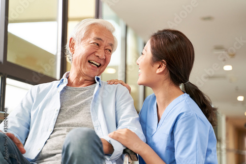 Fototapeta young friendly asian female caregiver talking to elderly man in nursing home obraz