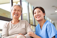 Portrait Of Happy Nursing Home Resident And Caregiver