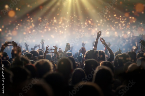 Stage lights and crowd of audience with hands raised at a music festival Canvas Print