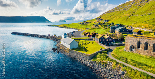 View from flying drone. Aerial summer view of Kirkjubour villagewith Hestur Island on background. Picturesque morning scene of Faroe Islands, Denmark, Europe. Beauty of nature concept background.