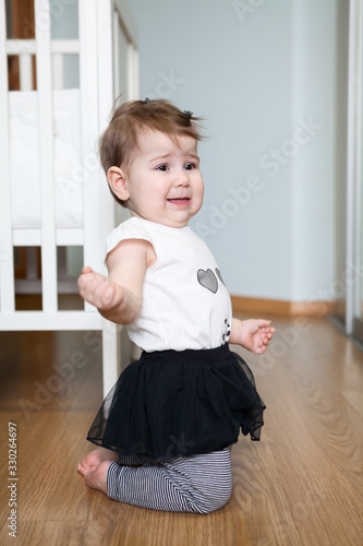 Photo Little capricious child standing on floor of domestic room, screaming and crying