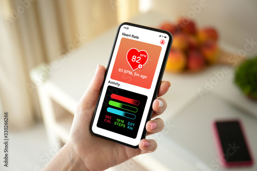 Photo female hand holding phone with app heart and activity