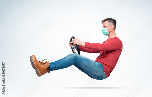 Obraz Man in respiratory mask drives a car while holding a steering wheel. Attention virus concept - fototapety do salonu