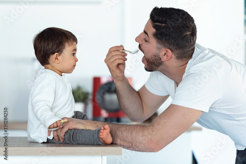 Handsome young father feeding his baby son in the kitchen at home Wallpaper Mural