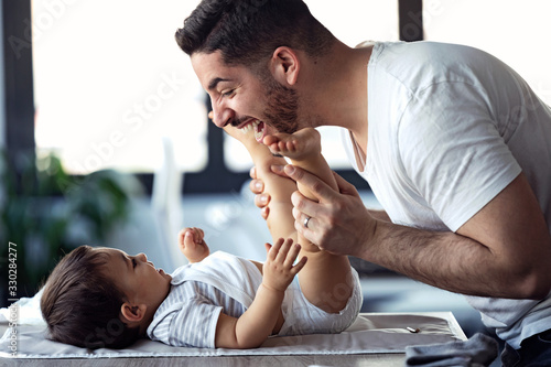 Smiling young father has fun with little baby while changing his nappy at home Fototapet