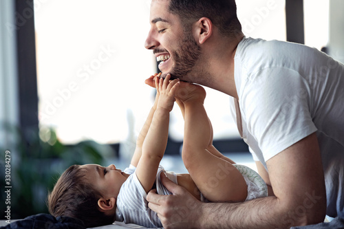 Canvastavla Smiling young father has fun with little baby while changing his nappy at home