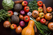 onions, garlic, tomato, greens, parsley, arugula, cabbage, apples, beetroot, carrots, pumpkin, lie on a wooden table