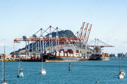 Photo TAURANGA, NEW ZEALAND - MARCH 6, 2020: Cargo ships docked into Tauranga Harbour Port waiting for the adjacent container cranes to load