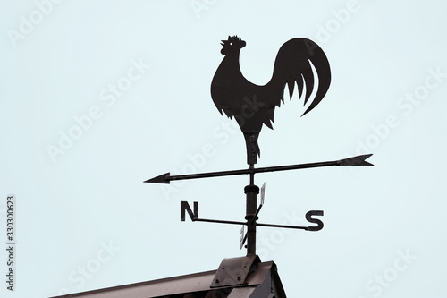 Wind vane on the roof in the form of a rooster, indicating the cardinal points Canvas Print
