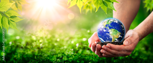 Photo Hands Holding Planet Earth On Soil In Lush Green Environment With Sunlight - The
