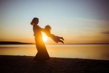 Banner With Silhouette Of Mom And Baby On A Sunset Background. Beautiful Landscape Suitable For Wallpaper. The Theme Of Love And Motherhood.