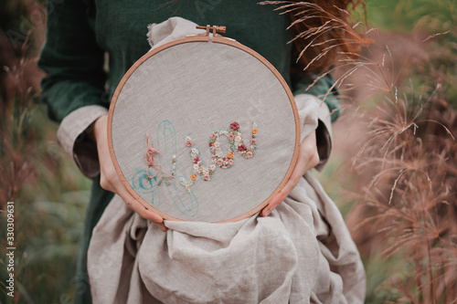Hands of girl / woman / female in boho linen dress hold sewing stitching pattern in embroidery frame on the background of park Fototapet