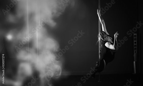 The dancer on the pylon in the studio. Girl doing exercises on a sports equipment.