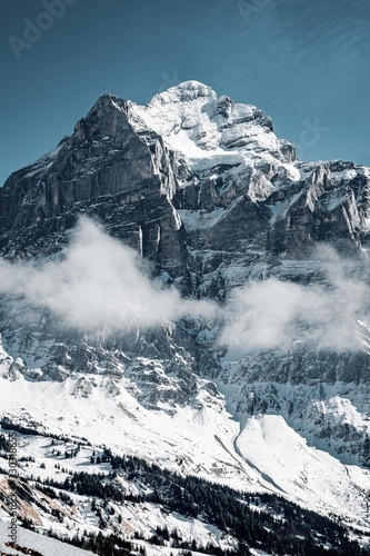 Beautiful shot of the snowy mountains surrounded by clouds Wall mural