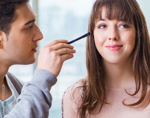 Photo Man doing make-up for cute woman in beauty salon