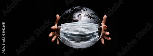 Obraz Kid holding globe map sphere isolated on black horizontal background. Ecological problems disasters. COVID-19 pandemic infection disease concept image, copy space for text - fototapety do salonu