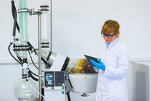 Chemist Working On Tablet Next To Rotavapor Machine In Laboratory