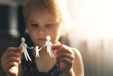 little girl with paper family in hands. concept of divorce, custody and child abuse