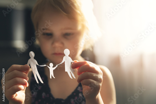 Obraz little girl with paper family in hands. concept of divorce, custody and child abuse - fototapety do salonu