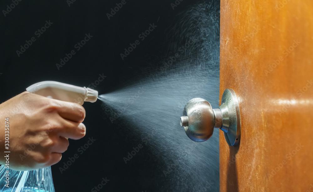 Fototapeta Cleaning door knob with alcohol spray for  Covid-19 (Coronavirus) prevention.