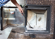 Man Cleaning Fireplace From Ashes