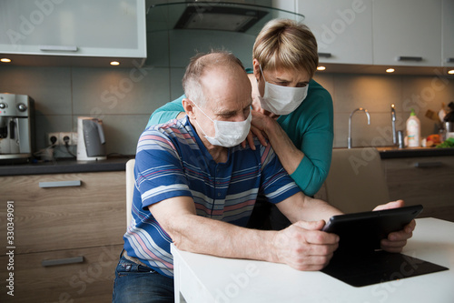 Seniors couple wearing medical face mask and using tablet at home. quarantine. health concept. Corona Virus. order of products online