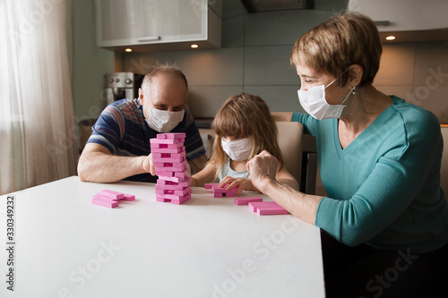 Obraz grandparents with granddaughter wearing medical face mask playing  board game together at home. quarantine. health concept. Corona Virus.  - fototapety do salonu