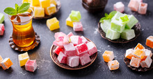 Assortment Of Turkish Delights With Glass Of Tea. Grey Background.